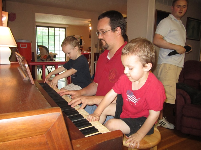 kids playing piano with dad